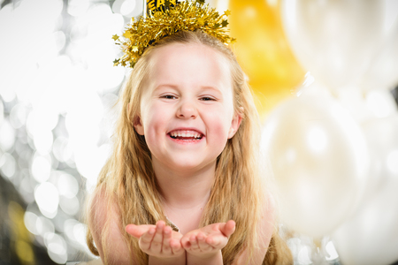 Little beautiful girl at a party New Year with balloons. Фото со стока