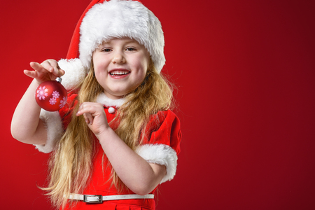 Little beautiful girl dressed as Santa Claus gifts dealer.