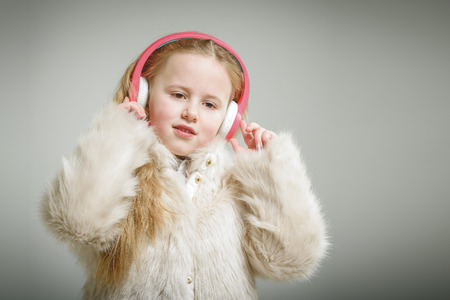 Party girl in pink fur coat and headphones. Фото со стока
