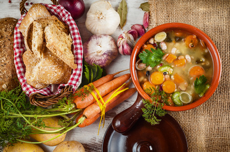 Rural vegetarian broth soup with colorful vegetables and rustic clay pot.