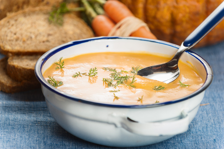 Soup with pumpkin and carrot on a blue tablecloth in country style