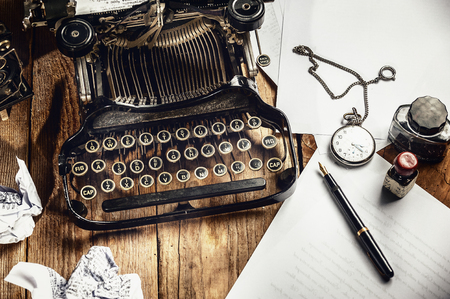 Text prescribed on a vintage typewriter and watch timekeeper.