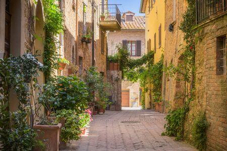 Sonnige Straßen mit bunten Blumen mit kontrastierenden Schattierungen. Spazieren Sie durch die toskanische Stadt