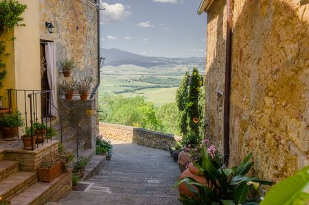 Sunny streets with colorful flowers with contrasting shades. Walk the Tuscan town