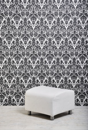 pouf: white leather pouf against vintage style wallpaper in studio