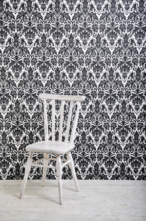white wooden chair against vintage style wallpaper in studio photo