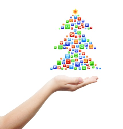 Right hand holding Christmas eve tree, made from application icons, isolated on white photo