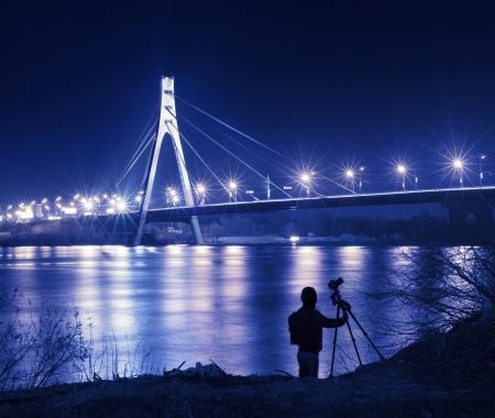 amateur: Silueta del fotógrafo con cámara y trípode frente a puente en la noche