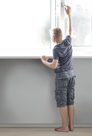 Young boy opening big window and looking forward, rear view photo