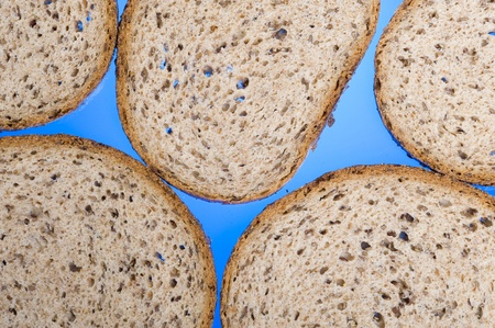Brown bread slices on blue background  Фото со стока