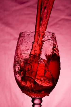 Red wine pouring intro Glass on dark background