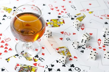Glass with cognac on background playing card