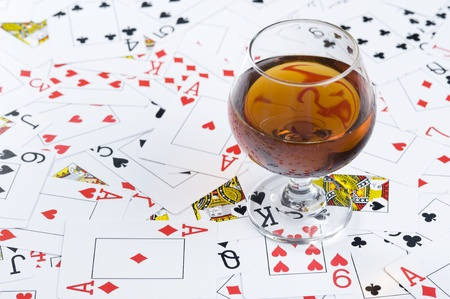 Glass with cognac on background playing card  Editöryel