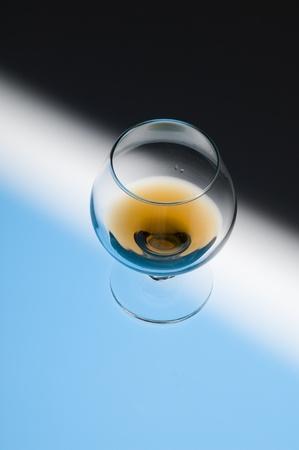 Glass with cognac on creative black background  Stok Fotoğraf