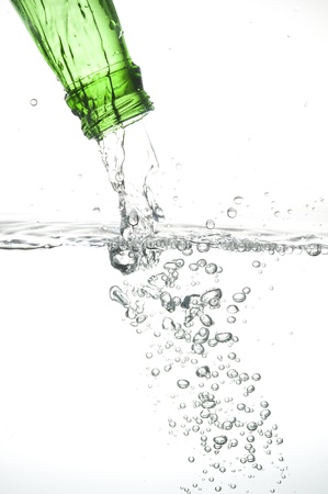 Green bottle with creative splashing blue water  photo