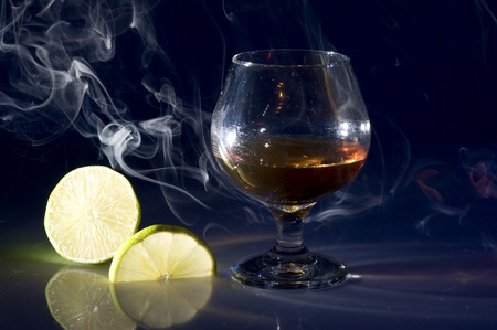 Glass with cognac and lime on creative black background  Stok Fotoğraf