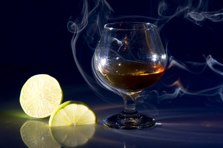Glass with cognac and lime on creative black background