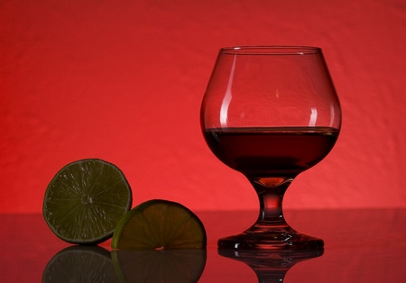 Glass with cognac and lime on red background