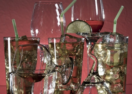 Glass with alcohol and ice on red background