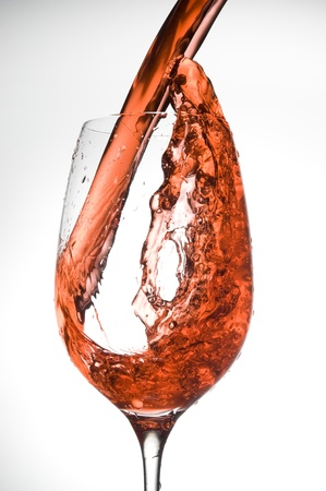 Red wine being poured intro glass isolatet on white