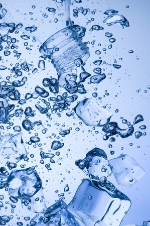 solid blue background: Mineral water with ice. Creative splashing blue water  Stock Photo