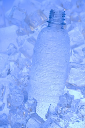 Mineral water with ice. Blue background with plastic bottle