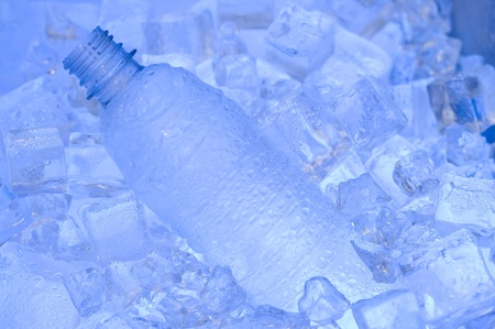 Mineral water with ice. Blue background with plastic bottle  photo
