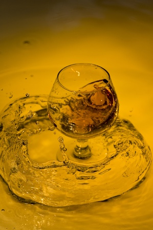 Class of brandy on creative brown background with water  photo