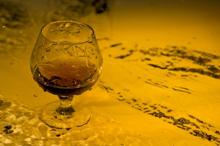 Class of brandy on creative brown background with water  Stok Fotoğraf