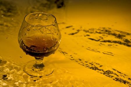 Class of brandy on creative brown background with water Zdjęcie Seryjne