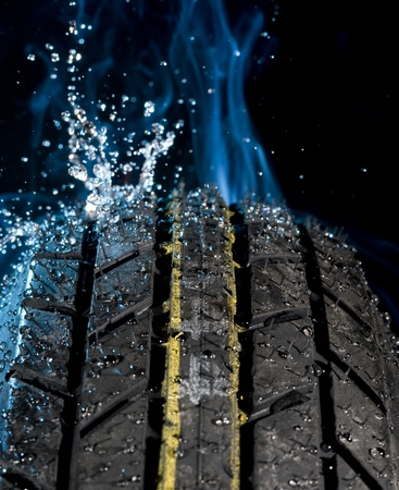 torrential: Tire with water drops on it smoke background