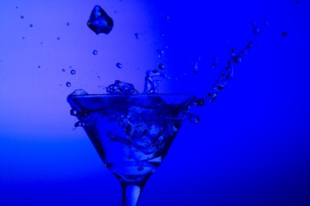 Splashing cocktail on the blue background