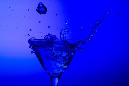 Splashing cocktail on the blue background