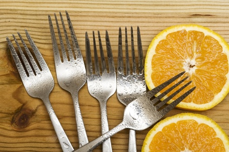 Orange with fork on woood background  Фото со стока