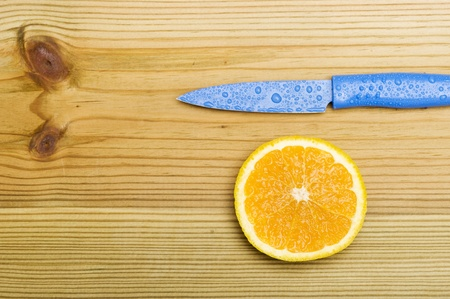 Orange with knife on woood background