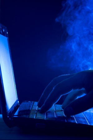 Laptop and human hand on blue background