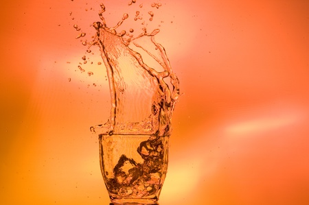 Whisky and ice. Splashing scotch on brown background