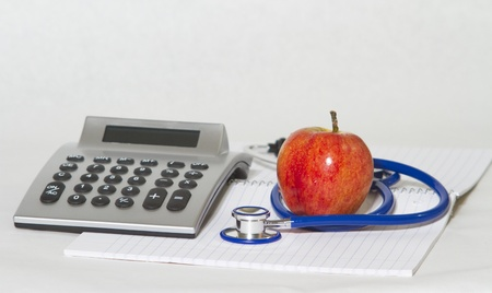 Stethoscope and calculator on the white background Banco de Imagens