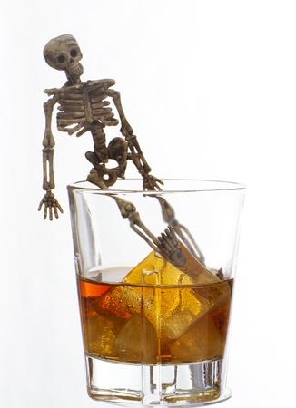 Esqueleto con un Whisky. Alcoholismo problema Foto de archivo