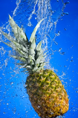 Pineapple with splashing water on blue background  photo