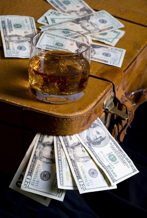 Dollar sticking out of overfilled case and whisky  Stock Photo