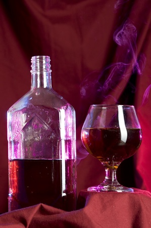 Glass with cognac on luxury red background Zdjęcie Seryjne