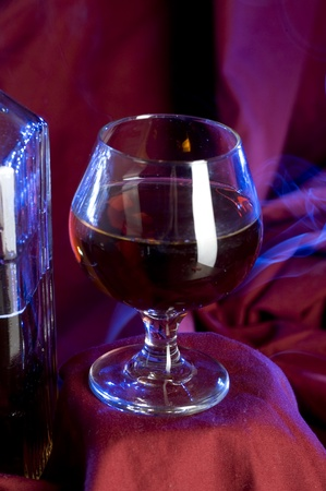 Glass with cognac on luxury red background