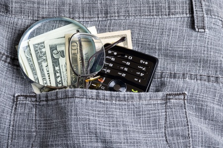 Cell phone in jeans pocket  and dollar Stock Photo - 12229630