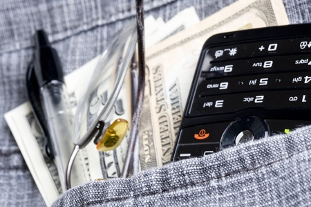 Cell phone in jeans pocket  and dollar  photo