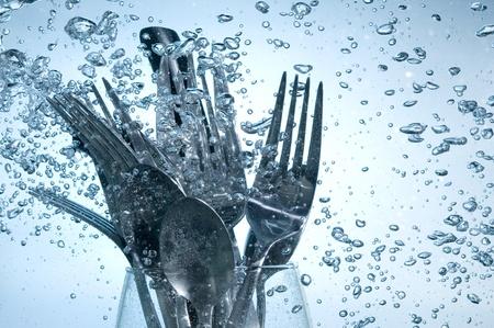 lavaplatos: Lavado de utensilios de cocina en el agua clara sobre fondo burbujas