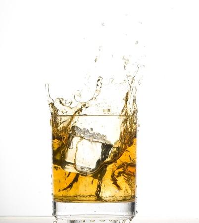 Whisky en ijs. Bruin brandewijn met opspattend