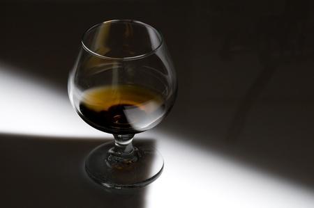 Glass with cognac on creative black background  Reklamní fotografie