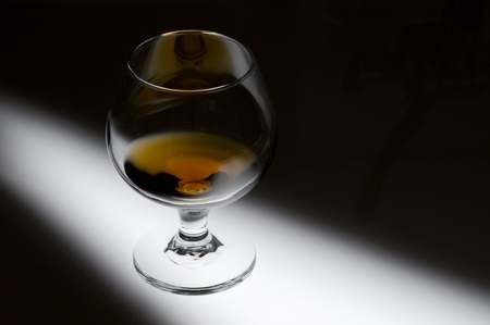 Glass with cognac on creative black background  Stock Photo