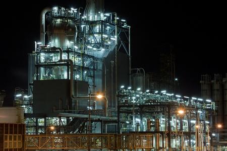 refinería de petróleo: Petroquímica de dispositivos y tuberías en la noche Editorial